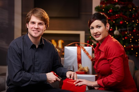 Young couple sitting on couch at home, wrapping christmas gifts together, smiling.   photo