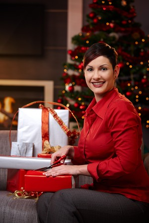 Young woman sitting on couch at home, wrapping gifts at christmas, smiling.   photo