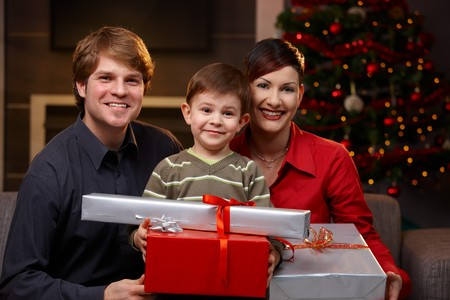 Portrait of little boy and happy parents holding christmas presents, smiling. photo