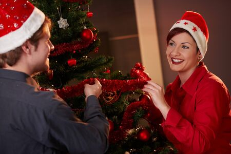 Happy young couple wearing santa claus hat, celebrating christmas, smiling.   photo