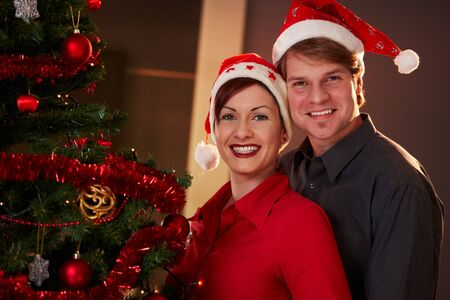 Portrait of happy young couple wearing santa claus hat, celebrating christmas, smiling. photo