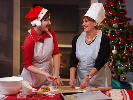 Happy mum and daughter laughing at baking christmas cake. photo