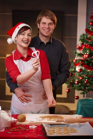Portrait of happy couple laughing at camera while baking christmas cake. photo