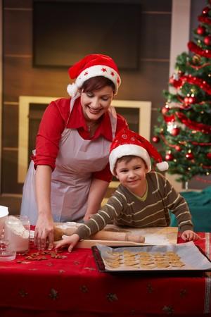 galletas de jengibre: Madre e hijo hornear el pastel juntos para Navidad, sonriendo.