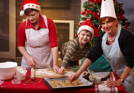 Grandmother, mum and son making christmas cake together at home, smiling. photo