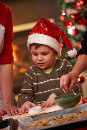 Small boy in santa claus hat helping at christmas baking watching mother and grandmother making cake. photo