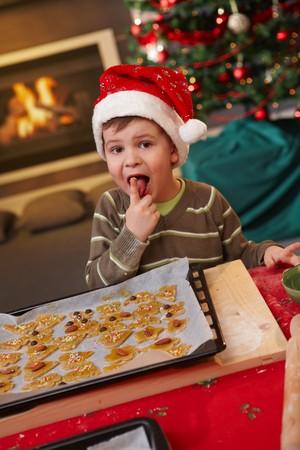 living room boy: Small boy wearing santa claus hat tasting christmas cake, looking at camera. Stock Photo