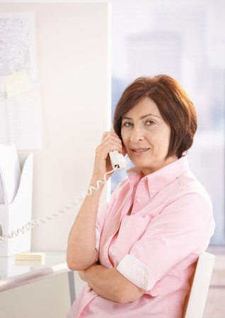 Portrait of mature office worker talking on landline phone at desk, looking at camera. photo