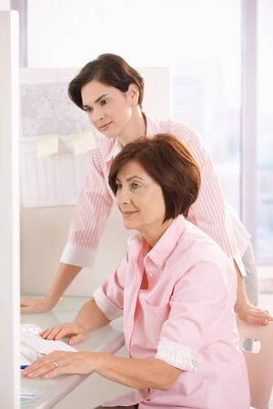 Female coworkers working together with computer in office. Stock Photo - 7792215