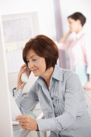 Mature office worker woman using landline phone, smiling, coworker using mobile phone in background. photo