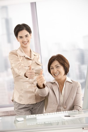 Smiling businesswomen giving thumb up in office Stock Photo - 7792207