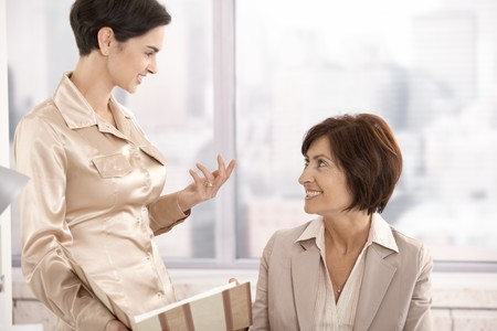Professional women in discussion in office, working with documents, smiling. Stock Photo - 7792214