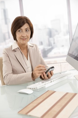 Mature businesswoman using smartphone, sitting at desk, smiling. photo
