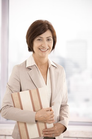 Senior businesswoman smiling, standing in office, holding folder in arm, looking at camera. photo