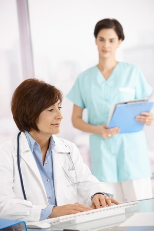 Senior female medical doctor working at desk with assistant standing in background. photo