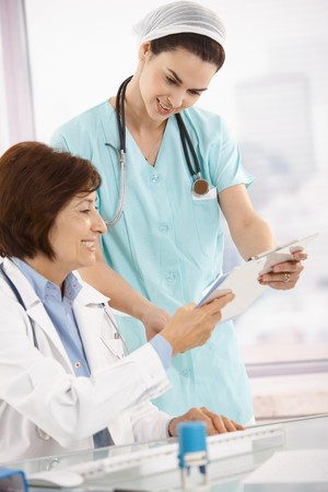 co worker: Smiling physician working with nurse, reviewing test at desk.