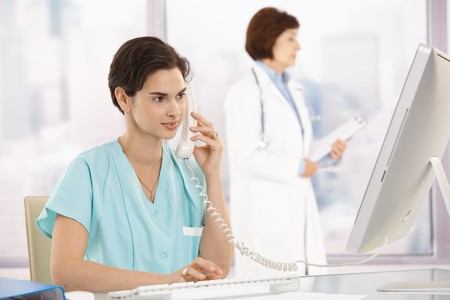 Medical assistant sitting at desk, talking on landline phone, using computer, doctor in background. photo