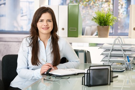 Smiling girl working in office sitting at desk with organizer, looking at camera. photo