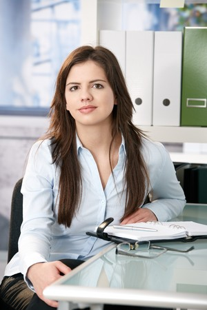 Attractive woman sitting at office desk with organizer, looking at camera, smiling. photo