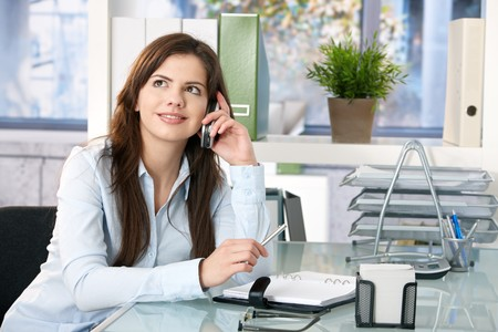 Female assistant sitting in office, speaking on mobile phone, looking up, smiling, holding pen. photo