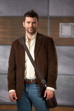 Portrait de jeune professionnel debout dans le hall de bureau avec sac d'ordinateur portable sur l'épaule.