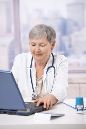 Senior female doctor, working at desk, using laptop computer. Looking at screen, smiling. photo
