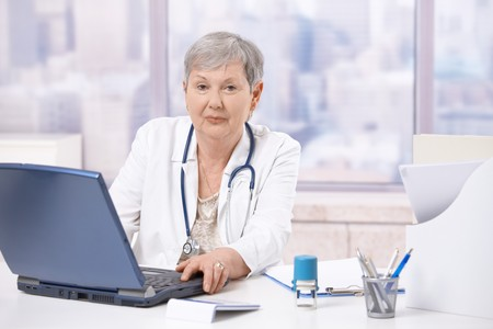 Senior female doctor, working at desk, using laptop computer. Looking at camera. photo