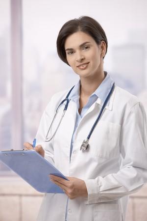 administrativo: Atractivo doctor femenina de pie en el pasillo del hospital haciendo papeleo, mirando la c�mara.
