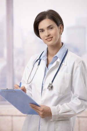 Attractive female doctor standing on hospital corridor doing paperwork, looking up at camera. Stock Photo - 7792403