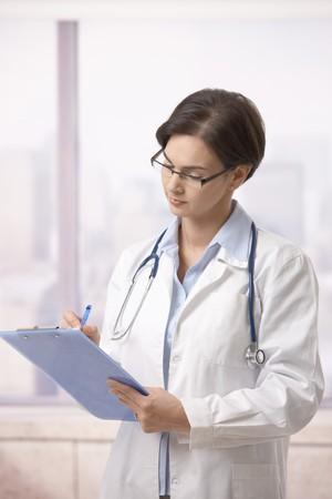 Attractive female doctor standing on hospital corridor doing paperwork. photo