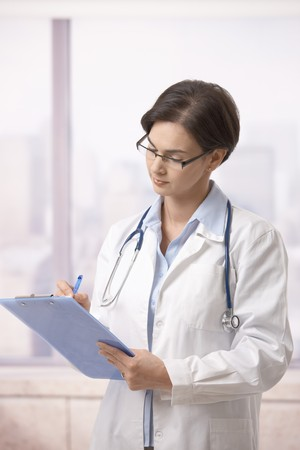 Attractive female doctor standing on hospital corridor doing paperwork. photo