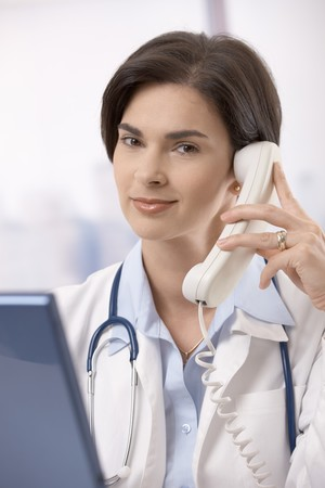 Mid-adult female doctor sitting behind computer and calling, looking at camera, smiling. photo