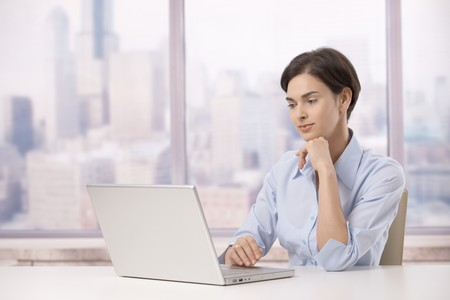 Professional woman sitting at skyscraper office working on laptop computer. photo