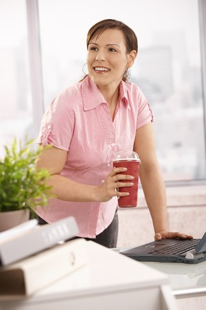 to go cup: Office worker leaning at desk holding coffee to go cup, looking up, smiling. Stock Photo