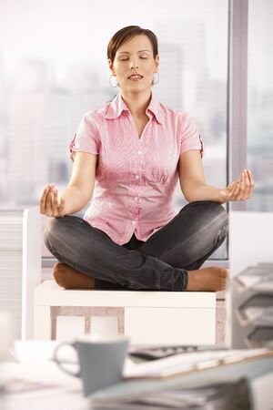 office cabinet: Young businesswoman sitting in lotus posture on office cabinet, meditating. Stock Photo