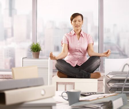 Relaxed office worker sitting on cabinet, doing yoga meditation with closed eyes, smiling.