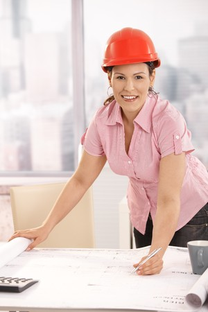 Young architect working at desk, writing notes to floor plan. Looking at camera, smiling. photo