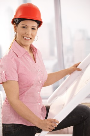Portrait of female architect holding floor plan, looking at camera, smiling. Stock Photo - 7792415