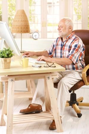 Senior man working in his study on desktop computer, smiling. Stock Photo - 7899210