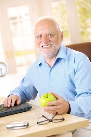 Active senior man sitting at desk at home, smiling, holding apple. Stock Photo - 7899183