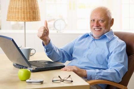 Happy senior man giving thumb up, sitting at desk using laptop computer at home. photo