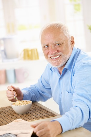 Portrait of healthy older man eating cereal for breakfast, looking at camera, smiling. Stock Photo - 7899190