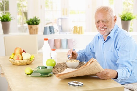 only one senior: Older man reading newspaper in kitchen while having cereal breakfast.