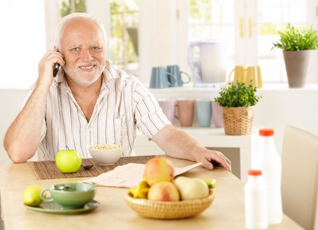 pensioner: Healthy pensioner using cellphone at breakfast table, smiling at camera. Stock Photo
