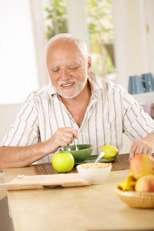 Happy senior man having tea in kitchen, reading morning newspaper. photo