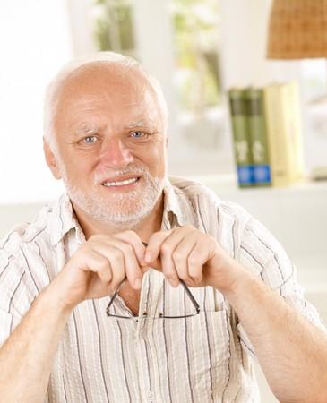 Portrait of white hair senior man holding glasses, smiling at camera. photo