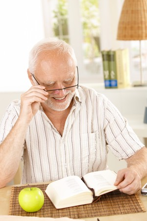 Laughing pensioner reading book, sitting at table at home. Stock Photo - 7899192
