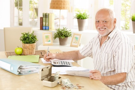 Active pensioner working at home, taking notes, sitting at table, smiling at camera. photo