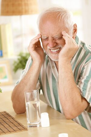Old man suffering from headache, eyes closed, grimacing from pain, taking painkiller sitting at table at home photo