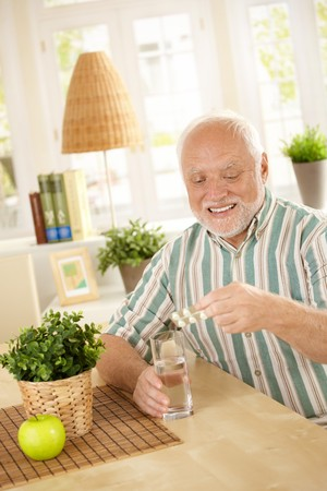 Smiling old man taking medication with water, holding bubble package, sitting at home. photo